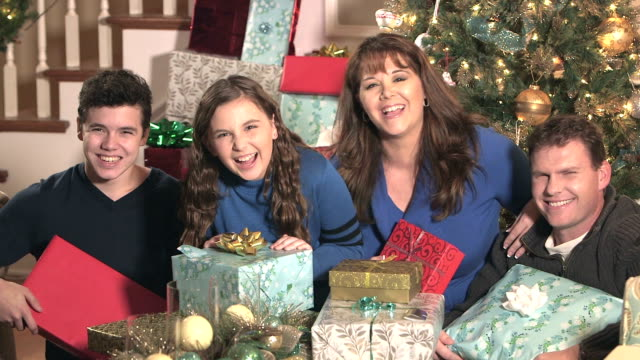 vídeos de stock e filmes b-roll de family of four laughing by the christmas tree - 14 15 years