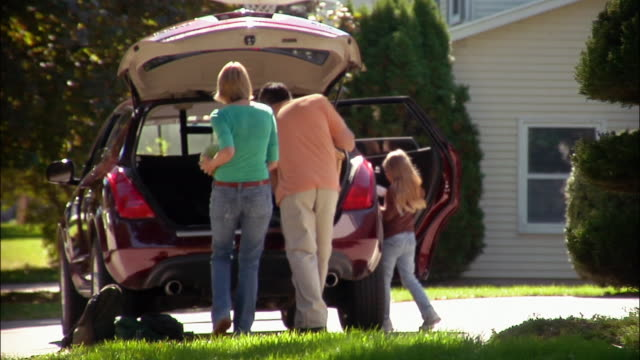 vidéos et rushes de family of four leaving house and carrying supplies to car / loading into trunk and getting into car / driving off - carrying