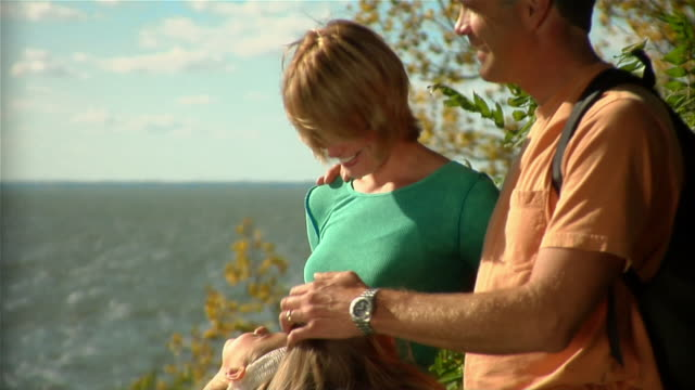 Family of four looking at scenic viewpoint of lake