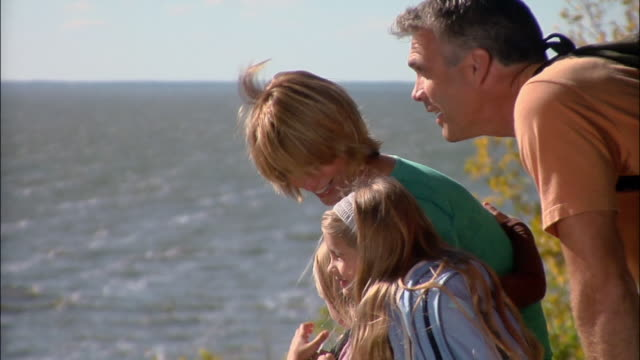 Family of four looking at view of lake