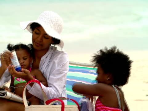 ms,  pan,  family of four on beach,  harbour island,  bahamas - sun cream stock videos and b-roll footage