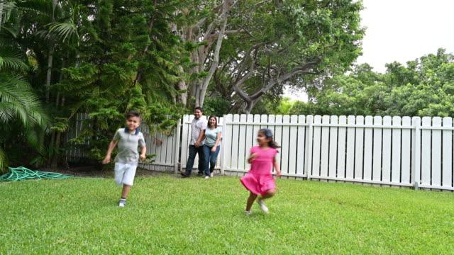vidéos et rushes de famille de quatre exécutant dans le beau jardin - clôture jardin