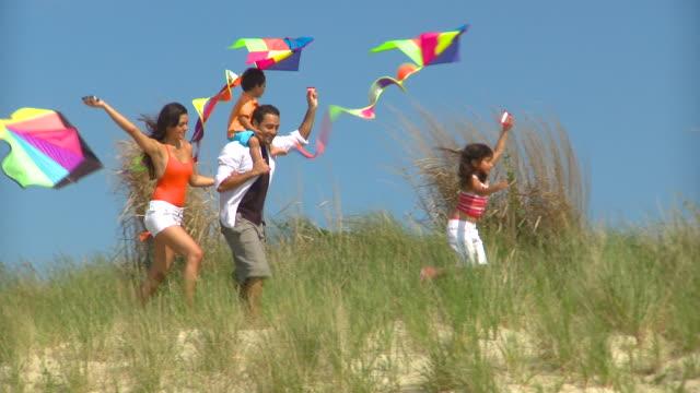 MS PAN Family of four running on sand dunes on beach, Eastville, Virginia, USA