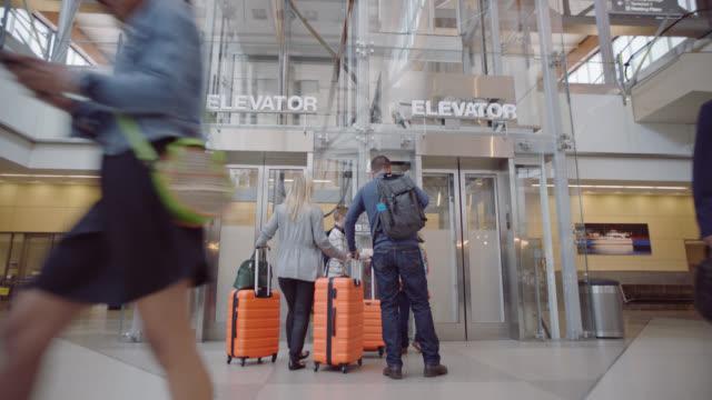 vídeos de stock e filmes b-roll de family of four rushes through crowd to elevator in airport terminal and gets on. - portão