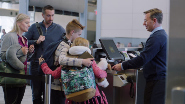 family of four rushes to airport terminal gate to scan their boarding passes just in time for flight. - biglietto aereo video stock e b–roll