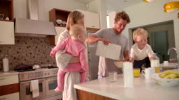 Family of Four Standing and Having Breakfast in Kitchen