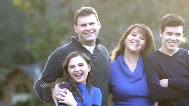 family of four standing together outdoors - two parents stock videos & royalty-free footage