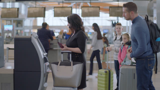 family of four waits anxiously to use check-in kiosk at ticket counter in airport terminal. - ticket counter stock videos & royalty-free footage