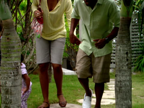 ms,  shaky,  family of four walking between palm trees in garden,  harbour island,   bahamas - fächerpalme stock-videos und b-roll-filmmaterial