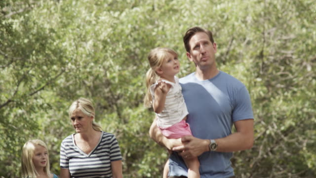 Family of four walking together as dad carries younger daugher.