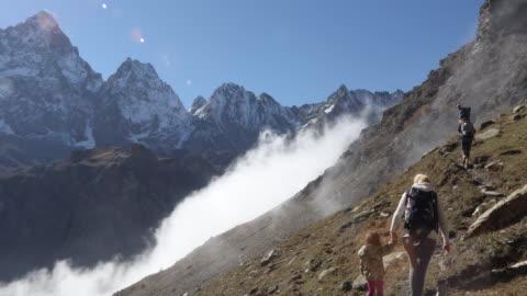 vidéos et rushes de famille de randonneurs monte la pente de la montagne au-dessus de la vallée - 4 5 ans