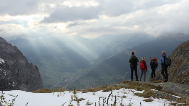 Family of hikers walk onto snowy ledge above valley, mountains