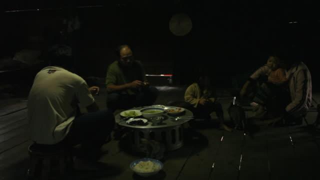 Family of Lao farmers eat dinner inside home