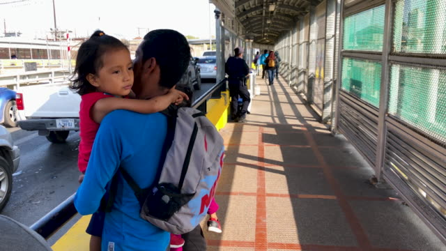 family of mexican asylum seekers walks to the center of the international bridge between mexico and the united states to officially request political... - einwanderer stock-videos und b-roll-filmmaterial