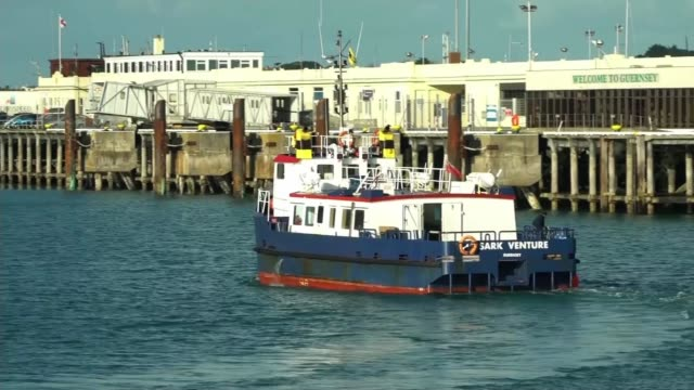 family of missing footballer fly over area where plane disappeared; channel islands: guernsey: ext buildings next to harbour small boat out of... - guernsey stock videos & royalty-free footage
