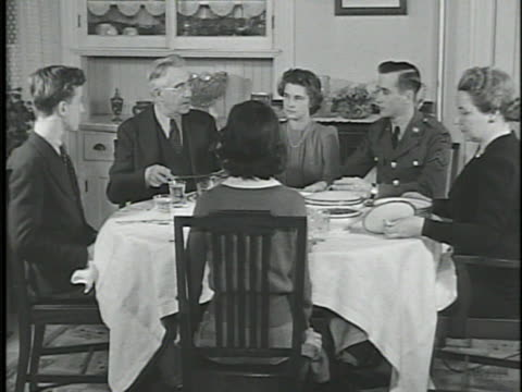 family of six at dinner table 'father' carving roast two young adults w/ male wearing military uniform 'mother' taking cover off dish female male... - roast dinner stock videos & royalty-free footage