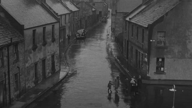 1950 ha family of six children walking along rain soaked streets in dreary area of town / united kingdom - foster care stock videos & royalty-free footage