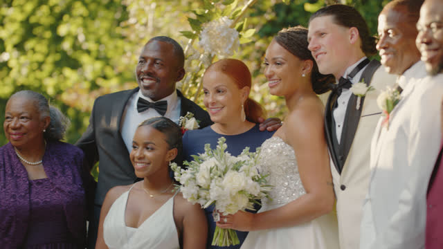 slo mo family of the bride gather outdoors for a family portrait - bunch stock videos & royalty-free footage