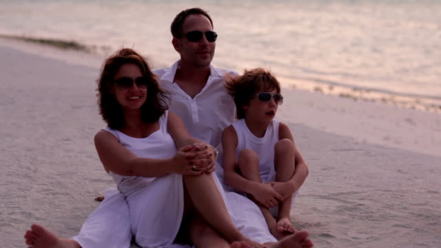 family of three close on a tropical beach