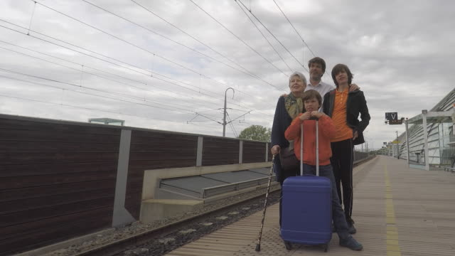 family of three generation waits on a station platform - stazione ferroviaria video stock e b–roll