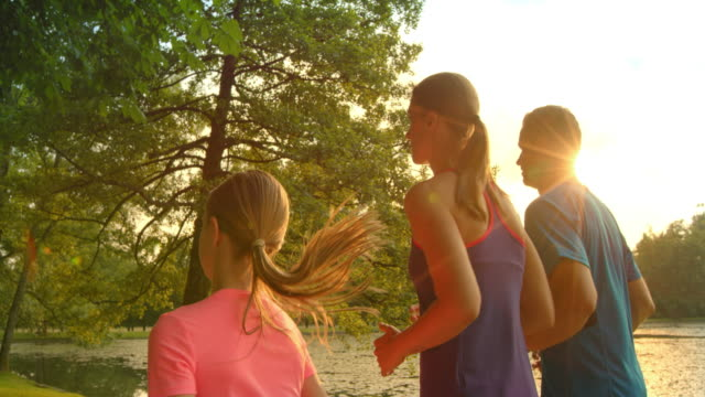slo mo ts family of three jogging in sunshine - jogging stock videos & royalty-free footage