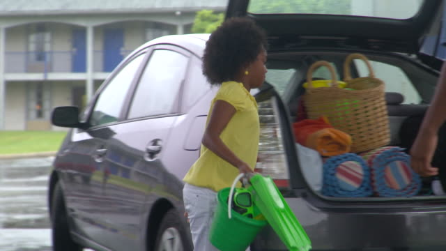 ms pan tu family of three unpacking car at parking lot in rain, eastville, virginia, usa - eastville stock videos and b-roll footage