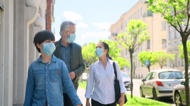 family of three wearing masks outdoors during 2020 pandemic - biological process stock videos & royalty-free footage
