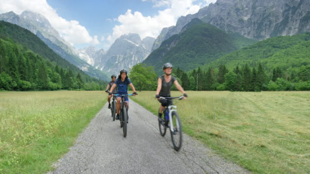 cs family of three with a teenage son cycling in a green mountain valley - mountain bike stock videos & royalty-free footage