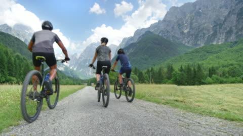 cs familie von drei mit einem teenager-sohn radfahren das grüne bergtal - exploration stock-videos und b-roll-filmmaterial