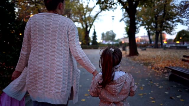family of two walking in a city park in autumn - rucksack stock videos & royalty-free footage