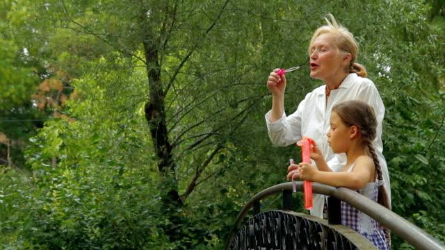 vidéos et rushes de famille sur un pont dans un parc - nurse