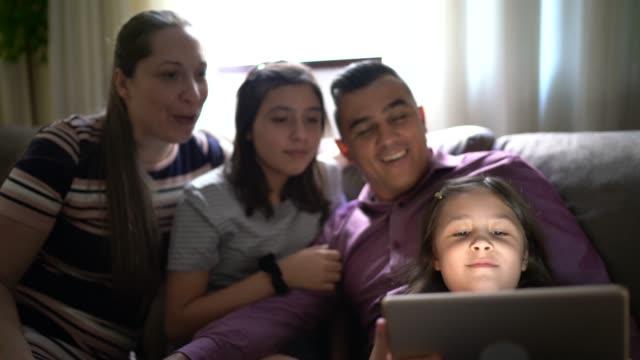 vídeos de stock, filmes e b-roll de família em uma chamada de vídeo com um tablet digital em casa - aconchegante