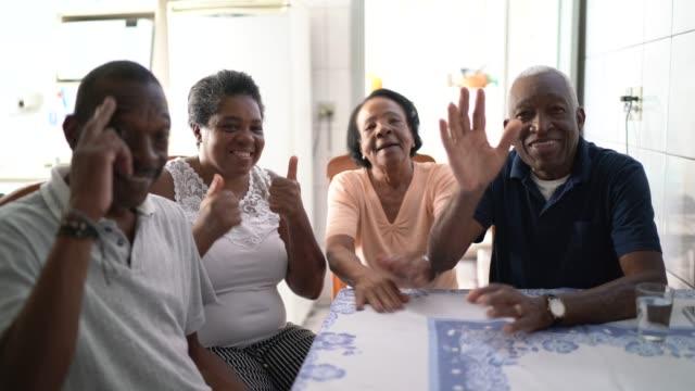 stockvideo's en b-roll-footage met familie op een video het roepen gebruikend laptop thuis - looking at camera