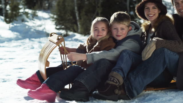 family on a wooden sled