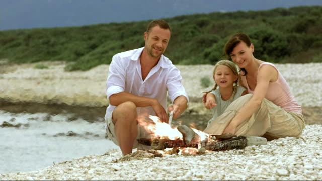 vídeos y material grabado en eventos de stock de familia en la playa mientras disfruta junto al fuego - falda