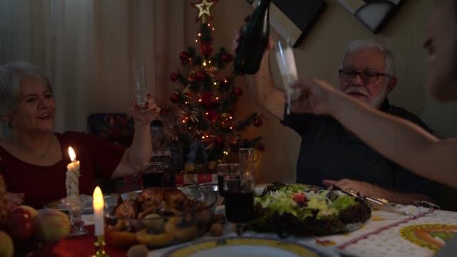vídeos y material grabado en eventos de stock de familia en celebración brindis en la cena de navidad - cena con amigos