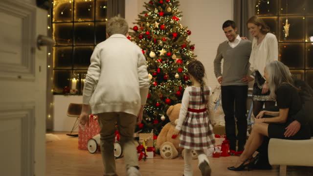 family on christmas eve distributing presents - christmas gift stock videos and b-roll footage