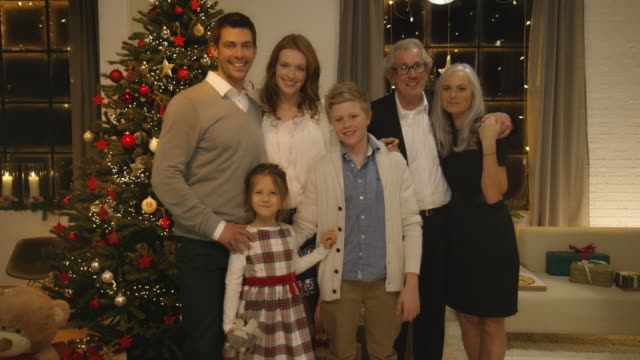 family on christmas eve in front of the christmas tree - photograph stock videos & royalty-free footage