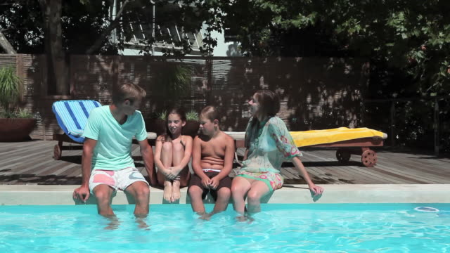 Family on edge of swimming pool