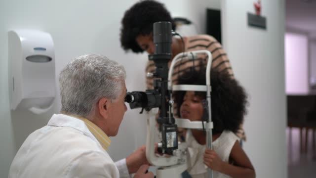 vídeos de stock, filmes e b-roll de família (mãe e filha) em consulta oftalmologista - afro