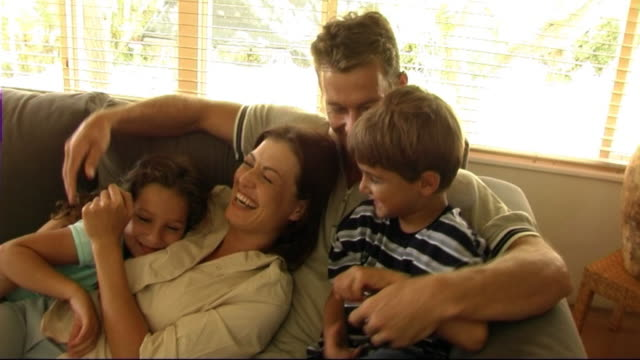 family on sofa cuddling and tickling - tickling stock videos & royalty-free footage