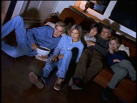 stockvideo's en b-roll-footage met family on sofa watching offscreen television - 1990 1999