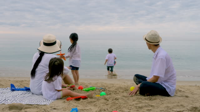 family on summer vacation playing on the beach building sand together.family, holiday and travel concept. - picnic stock videos & royalty-free footage