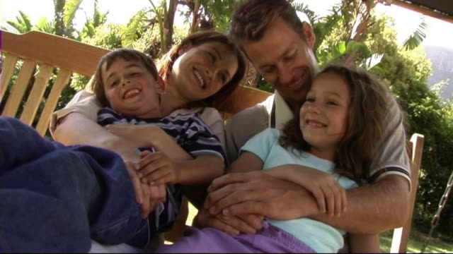 family on swing hammock, hugging - hängematte stock-videos und b-roll-filmmaterial