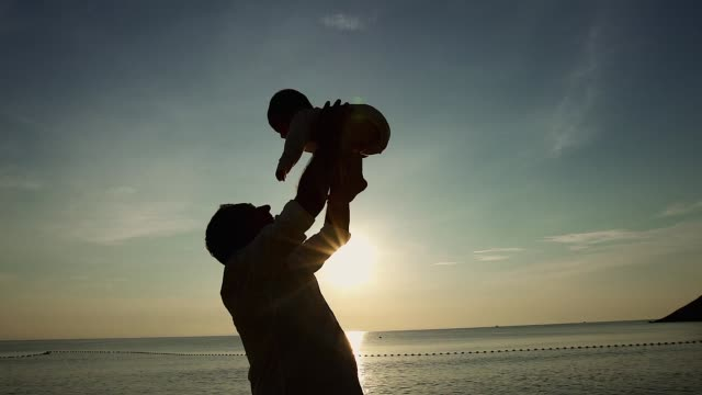 family on the beach concept, caucasian father playing and carrying his son on the tropical beach in the sunset. - carrying stock videos & royalty-free footage
