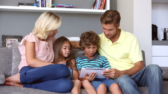 stockvideo's en b-roll-footage met family on the couch looking at tablet pc - middellang haar