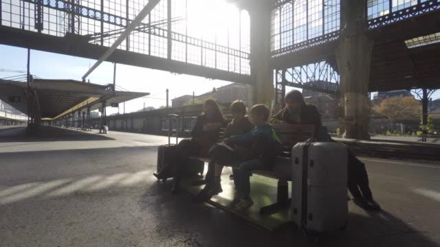 vidéos et rushes de family on the platform of a train station - valise