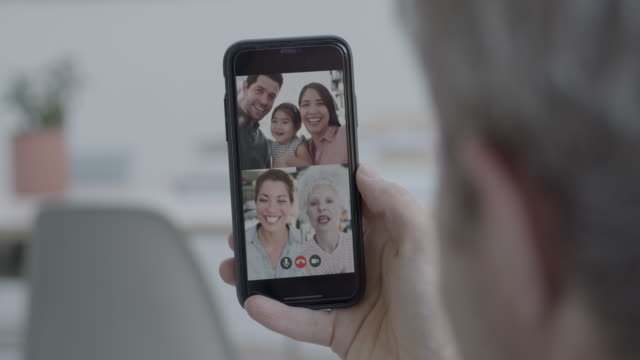 family on video call at home during social distancing using smart phone and video conferencing technology - bonding stock videos & royalty-free footage