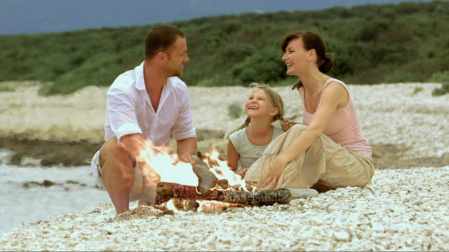 Family on white beach by the fire