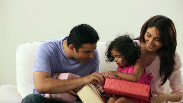 family opening packing of a gift box  - maharashtra stock-videos und b-roll-filmmaterial